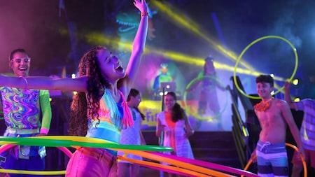 Visitante se divertindo com um bambolê no ritmo da música em um ambiente estilo casa noturna enquanto outras pessoas assistem