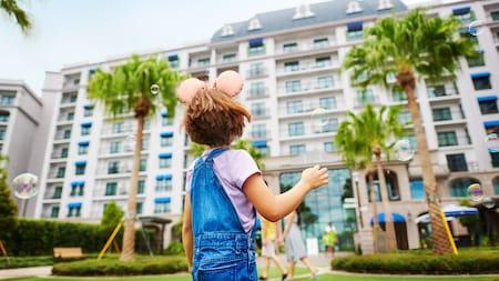 Little girl with Mickey ear headband looks toward Disney's Rivera Resort with bubbles around her