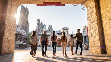 Una familia atraviesa un túnel en Star Wars Galaxy's Edge, una tierra con torres de madera petrificada y edificios al estilo de Star Wars