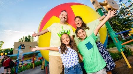 Una familia posa jocosamente frente a una pelota gigante y Tinkertoys en Toy Story Land