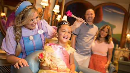 A stylist waving a wand over a girl in a princess dress at Bibbidi Bobbidi Boutique