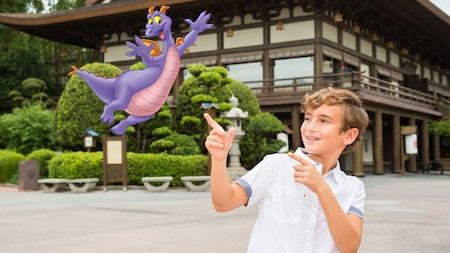 Un niño pequeño señala jocosamente una imagen superpuesta del dragón Figment