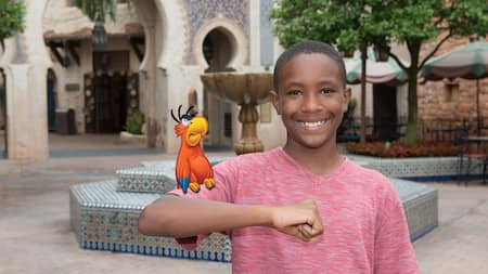 A young boy in the Morocco Pavilion is delighted to pose with the red and blue plumed parrot, Iago, perched on his arm.