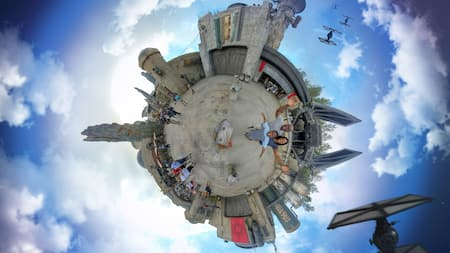 A special effects 360 degree aerial photo of a family at Star Wars Galaxy's Edge with Tie Fighters flying overhead