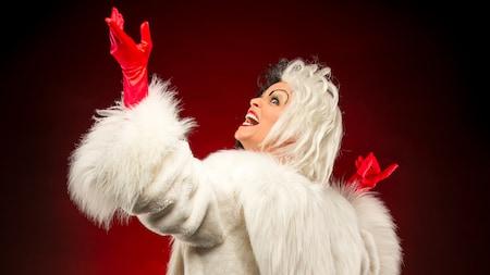 Cruella de Vil hace una pose malvada y gestos alocados con sus manos