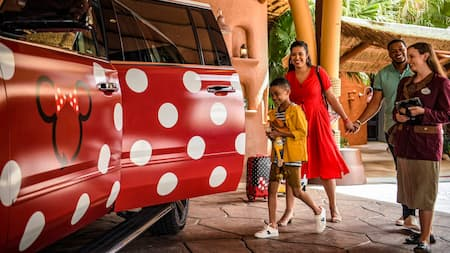 A family boards a Minnie Van service vehicle at a Disney Resort as a Cast Member looks on