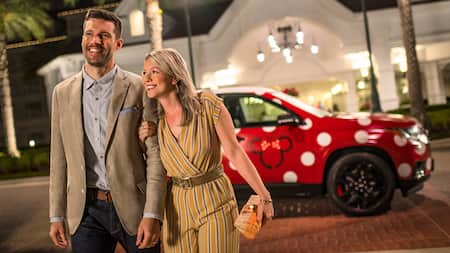 A smiling couple steps out of their Minnie Van service vehicle at night