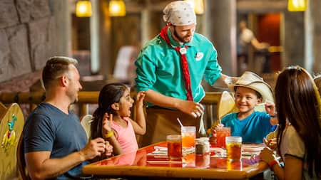 Un mesero en Whispering Canyon Café bromea con una familia mientras le pone su sombrero de vaquero a un niño