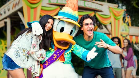 A man and a woman pose for a picture with Donald Duck at Donalds Dino Bash.