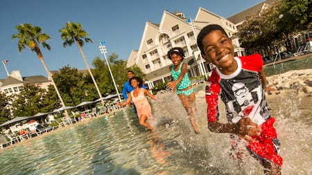 2 children and their parents playing in a swimming pool at Disney's Yacht Club Resort