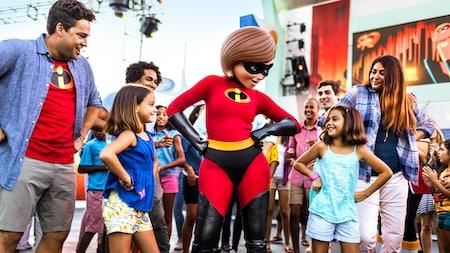 Mrs. Incredible con las manos en las caderas, parada con un grupo de Visitantes