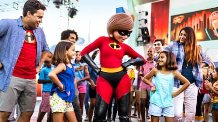 Mrs. Incredible with her hands on her hips, standing with a group of Guests
