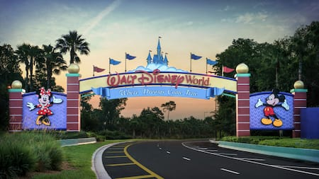 An archway with the words Walt Disney World flanked with characters goes over a 2 lane road