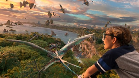 A boy flies on through the skies over Pandora on the back of a Banshee with the Na'vi