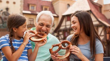 Um homem e 2meninas apreciando pretzels quentes e macios gigantes no pátio do Pavilhão da Alemanha do Epcot