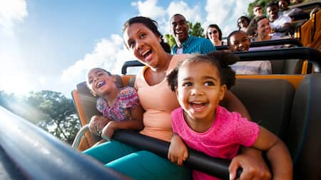 A woman and 2 girls smile and laugh as they ride a roller coaster