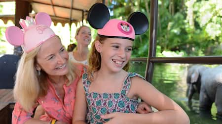 A woman and a girl, both wearing mouse ears, gaze out the side of a Jungle Cruise boat
