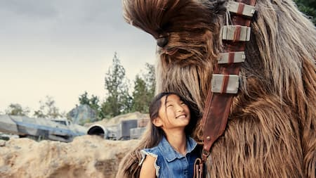 A girl smiles and looks up at Chewbacca as they hug in Star Wars: Galaxy's Edge