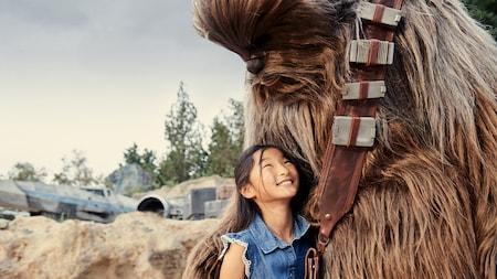 Uma menina sorri e olha para o Chewbacca enquanto eles se abraçam em Star Wars:Galaxy's Edge