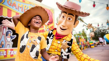 A young boy frolics with Woody, the cowboy from Toy Story, at Disney's Hollywood Studios