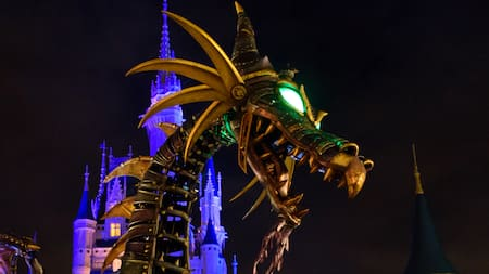 Maleficent passes Cinderella Castle in her dragon form at night