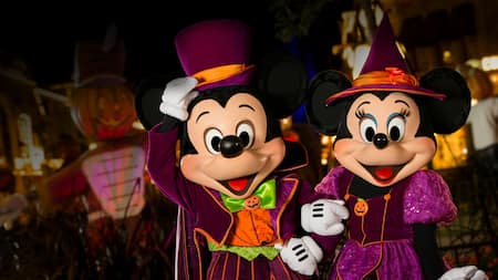 Mickey Mouse and Minnie Mouse dressed in Halloween attire standing near a scarecrow
