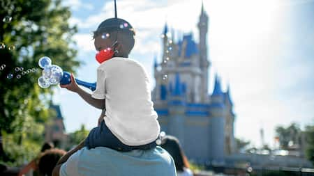 Little boy with a bubble wand sits on dads shoulders with Cinderellas Castle in the background
