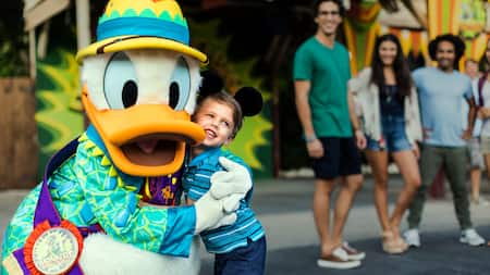 Donald Duck dressed in a safari outfit while hugging a young boy