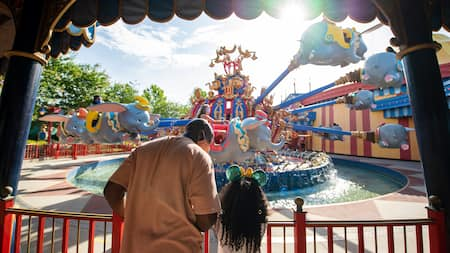 Dad and daughter look at Dumbo attraction while waiting in line