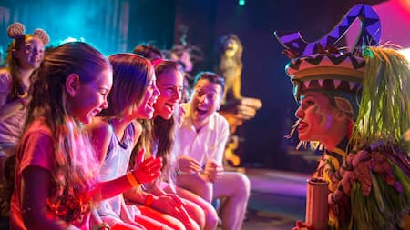 A Lion King performer bending down to greet 3 happy young girls in the audience