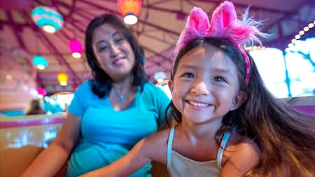 A little girl wearing a Disney headband smiles while her mom looks on