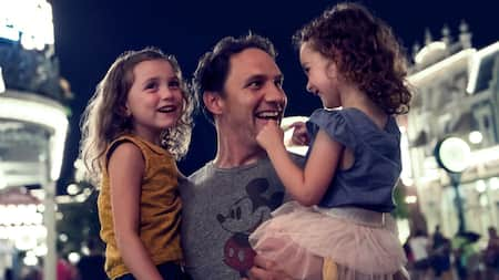 A man holds 2 smiling little girls