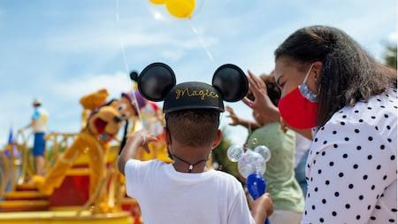 Un niño saluda a Pluto cuando pasa en un desfile