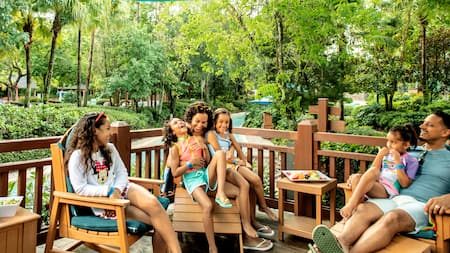 A smiling family lounging and enjoying snacks on a shaded deck