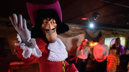 Captain Hook strikes a fiendish pose as families look on