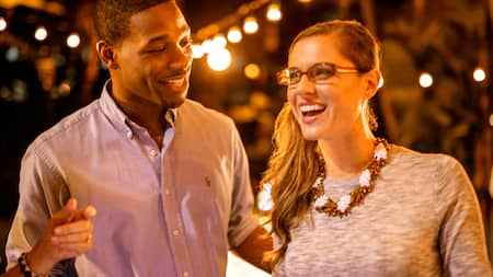 A man and woman smile together at night with many lights shining in the background