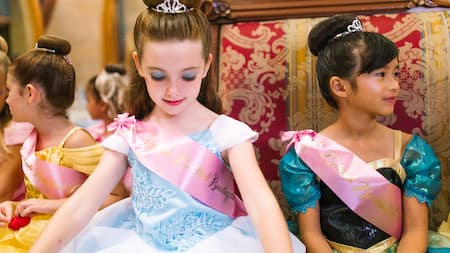 Young girls wearing princess gowns, sashes and crowns sit together