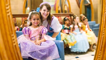 A young girl in a princess gown and her Fairy Godmother in Training smile at the mirror