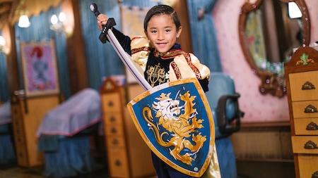 Um menino usando fantasia de cavaleiro mostra sua espada e escudo