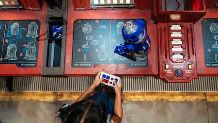 A young girl controls her new R series droid atop a workshop console featuring construction blueprints of droids