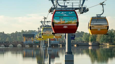 People ride the Disney Skyliner over a body of water near a bridge