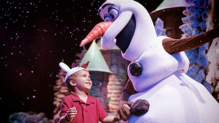 Olaf holds hands with a smiling boy wearing an Olaf hat
