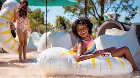 A girl smiles while sitting on a float at Disney's Blizzard Beach water park