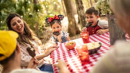 A girl in Minnie Mouse ears eats a Mickey ice cream bar while on a picnic with her family