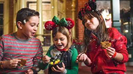 Three kids sit on Main Street USA eating dessert while snowflakes fall around them