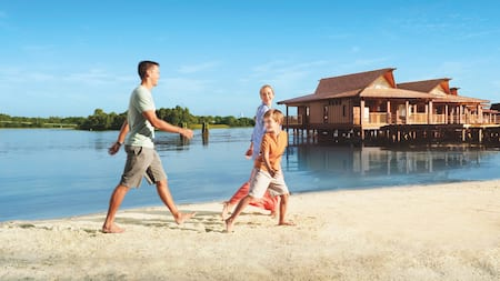 A happy family walks on the beach along Seven Seas Lagoon