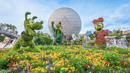 Topiaries of Pluto, Goof and Daisy Duck in front of Spaceship Earth at Epcot