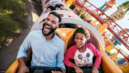 A boy and his father scream while riding Slinky Dog Dash in Toy Story Land