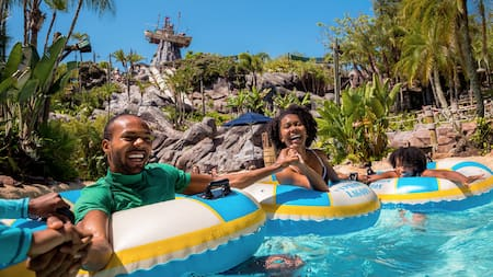 A family of 4 hold hands while relaxing on floats at Disney's Typhoon Lagoon water park