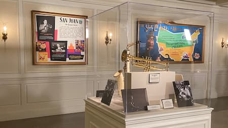 An exhibit in a gallery featuring a trumpet, saxophone, photos of musicians and 2 displays with the titles San Juan, and The Soul of Jazz, an American Adventure